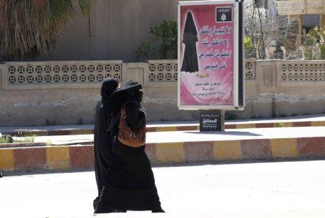 Γυναίκες στη Ράκκα με την υποχρεωτική αμφίεση που προβάλλουν ακόμα και σε αφίσες σε όλην την  πόλη