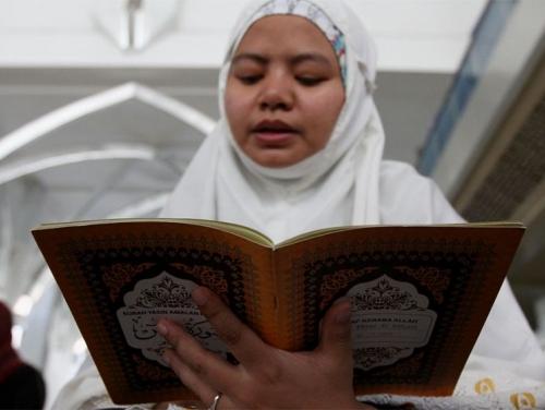 γονεας θυματος διαβαζει το Κορανι σε προσευχη για τα θυματα σε τζαμι της Μαλαισιας