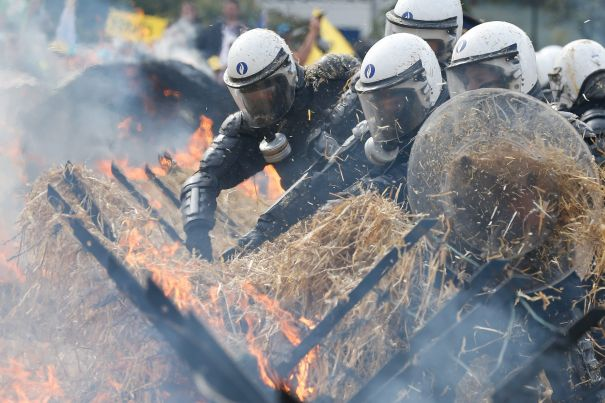 epa04918238 Belgian riot police officers try to extinguish a burning hay barricade as they guard the premises during a European farmers protest rally near the European institutions in Brussels, Belgium, 07 September 2015. Thousands of farmers, many withy their tractors, were gathering on the occasion of an European Agriculture ministers council meeting to vent their anger over economic problems in the agriculture sector and to protest against the decrease of their incomes and the increasing instability they are facing. EPA/LAURENT DUBRULE