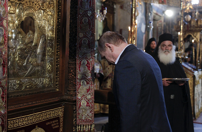 epa05333624 Russian President Vladimir Putin bows in front of an icon of Virgin Mary as he visits the church of the Protaton, dedicated to the Dormition of the Virgin, in Karyes, the administrative centre of the all-male Orthodox monastic community of Mount Athos, Greece, 28 May 2016. EPA/ALEXANDROS AVRAMIDIS / POOL