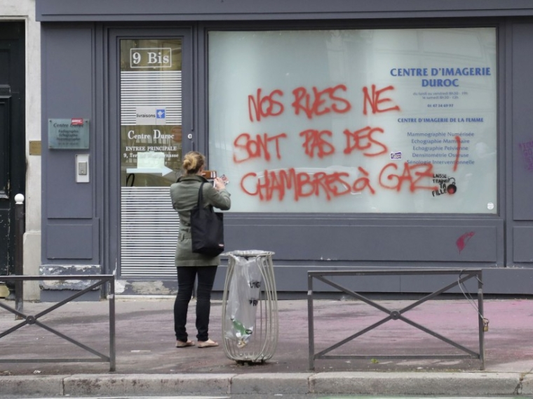 "A woman takes a picture on June 15, 2016 of graffiti, spray painted during a demonstration against labour reforms on June 14, reading ""Our streets are not gas chambers!"" on Boulevard du Montparnasse in Paris. / AFP PHOTO / Jacques DEMARTHON"