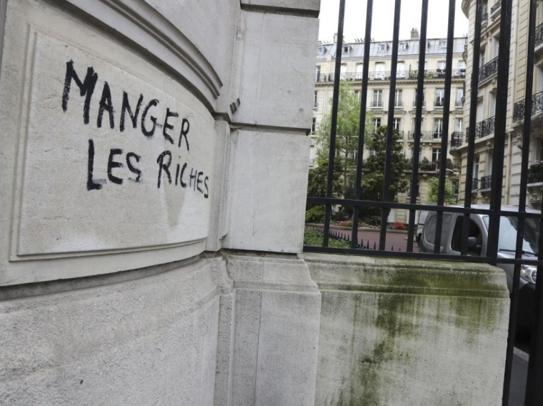 "A photo taken on June 15, 2016 shows graffiti, spray painted during a demonstration against labour reforms on June 14, reading ""Eat the rich"" on Boulevard du Montparnasse in Paris. / AFP PHOTO / JACQUES DEMARTHON"