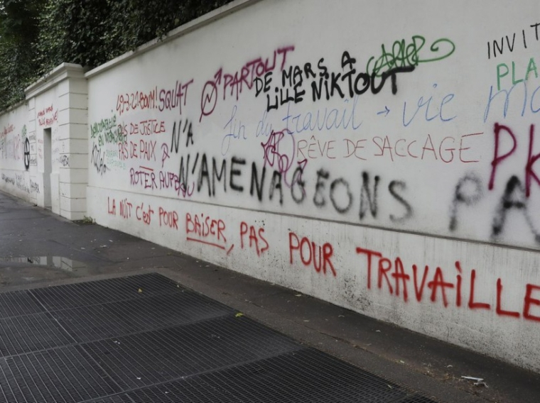 A photo taken June 15, 2016 shows graffiti, spray painted during a demonstration against labour reforms on June 14, covering a wall on Boulevard des Invalides in Paris. / AFP PHOTO / Jacques DEMARTHON