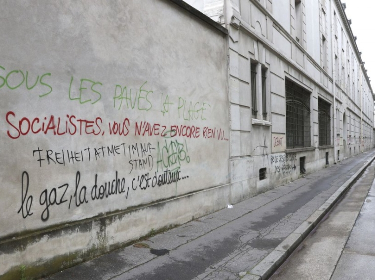 "A woman walks on June 15, 2016 past graffiti, spray painted during a demonstration against labour reforms on June 14, reading ""Socialists, you haven't seen anything yet..."" (L) near Victor Duruy high school on Boulevard des Invalides in Paris. / AFP PHOTO / Jacques DEMARTHON"