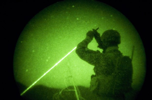 American soldiers with the 173rd battle company, on a battalian-wide mission in the korengal valley, Afghanistan. Through night-vision goggles: JTAC Kevin Caroon, 28, 'sparkles' a target for the AC130 pilots above as he helps control close air support fire from above Yakachina village while on a mission with Battle company in the Korengal Valley.  JTACs are Airforce-trained specialists in direct contact with the bomber pilots to call in airstrikes on certain targets while weighing and monitoring collateral damage potential. Captain Dan Kearney, the JTACs, and certain intelligence and communication specialists work as a team from afar but with a bird's eye view to help infantry troops on the ground. October 2007.
