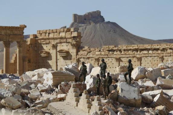 FILE PHOTO: Syrian army soldiers stand on the ruins of the Temple of Bel in the historic city of Palmyra, in Homs Governorate, Syria April 1, 2016. REUTERS/Omar Sanadiki/File Photo